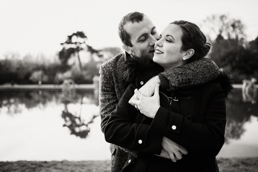 deux amoureux s'enlacent au bord de l'eau a Versailles